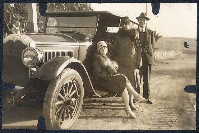 Un hombre y dos mujeres apoyándose en un automóvil