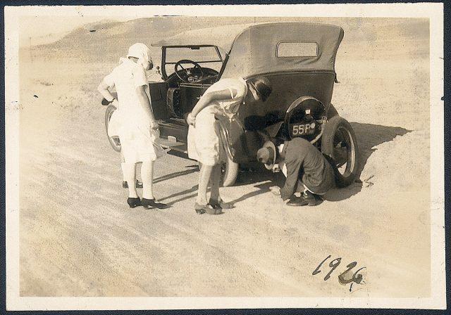 Dos mujeres y un hombre arreglando un automóvil