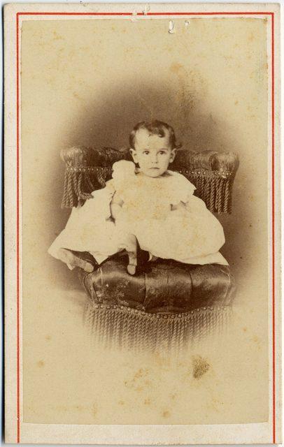 Retrato de un bebé sentada sobre un sillón.