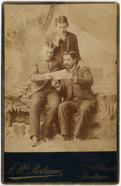 Retrato de tres hombres leyendo una hoja.