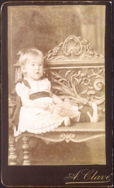 Retrato de bebé sentada sobre un banco.