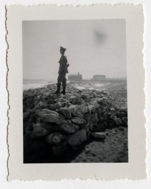 Soldado sobre una contención de roca en la playa