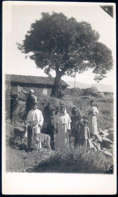 Hombres y niños delante un pisonay