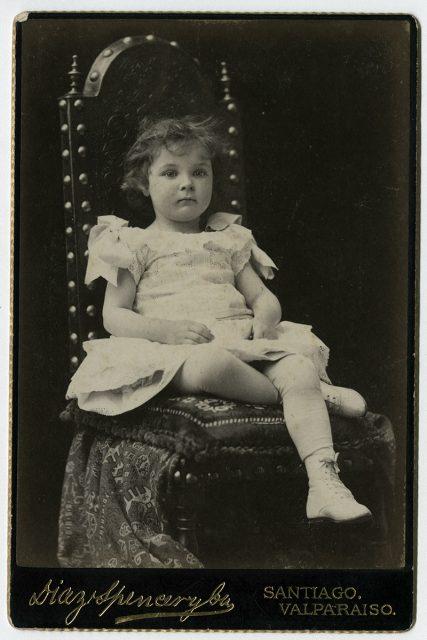 Retrato de una niña sentada sobre una silla