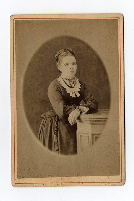 Retrato de una mujer apoyada sobre un mueble