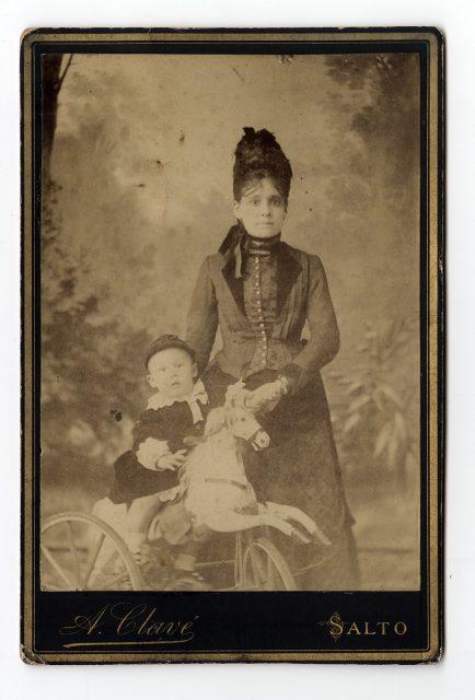 Mujer con su guagua sobre un caballo de madera