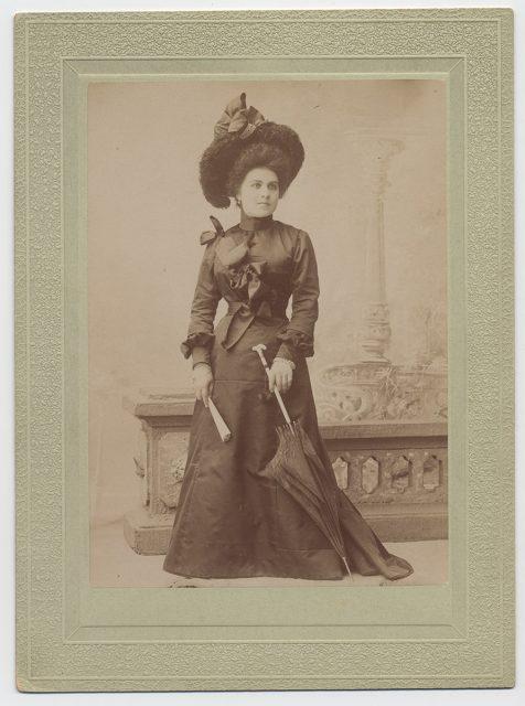 Mujer vestida de negro con sombrilla