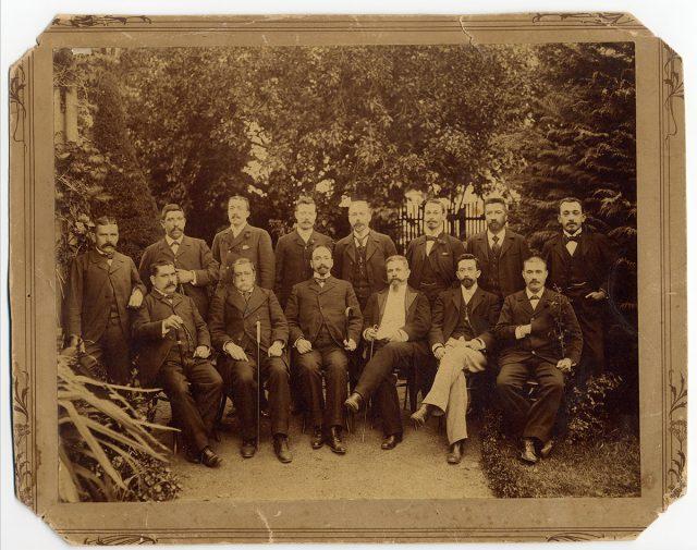 Grupo de hombres posando en un jardín