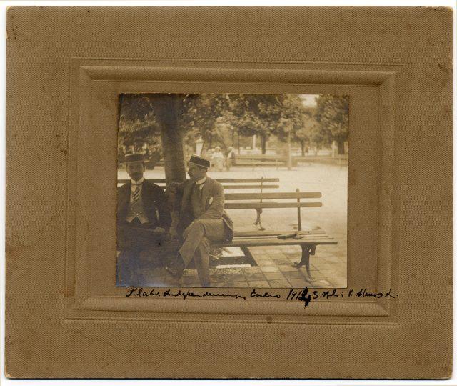 Dos hombre sentados sobre un banco a la sombra de un árbol
