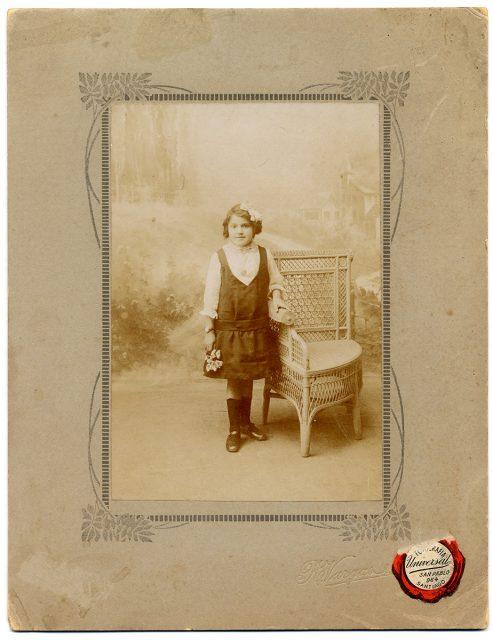 Retrato de una niña apoyada sobre una silla