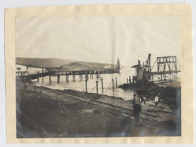 Hombres trabajando cerca del mar en la construcción de una línea de ferrocarril