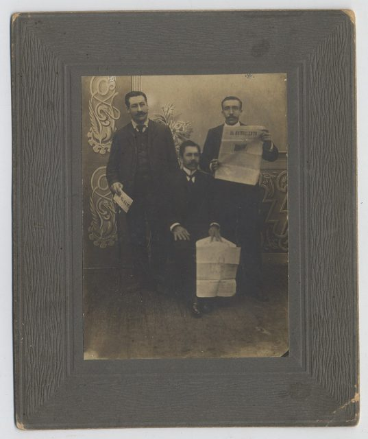 Tres hombres leyendo el diario «El Hambriento»