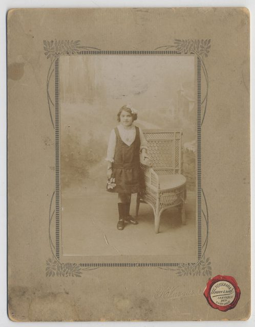 Retrato de un niña apoyada sobre una silla