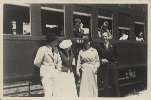 Grupo de personas afuera de un ferrocarril