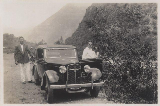Tres personas y su vehículo en un camino rural