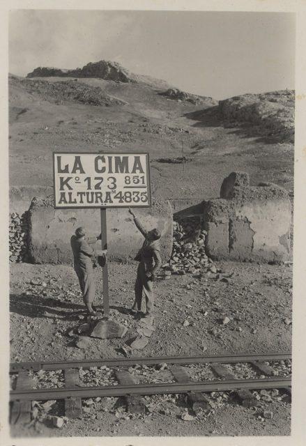Dos hombres al lado de un letrero