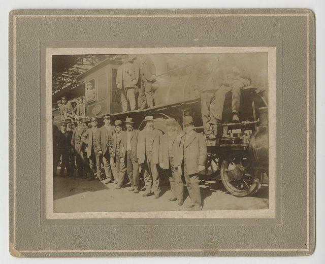 Jorge Toloza Flores y otros hombres junto a un tren.